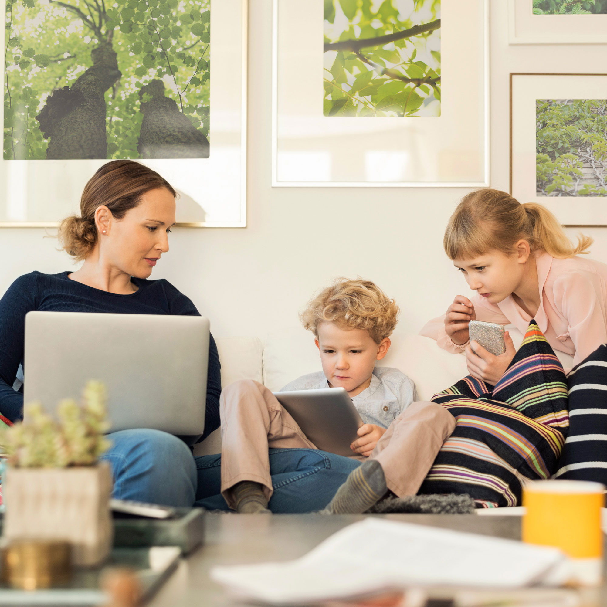 Mother with two children looking at different devices.